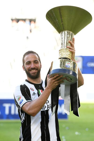 Gonzalo Higuain of Juventus FC celebrates with the trophy after the beating FC Crotone 3-0 to win the Serie A Championships at the end of the Serie A match between Juventus FC and FC Crotone at Juventus Stadium on May 21, 2017 in Turin, Italy.