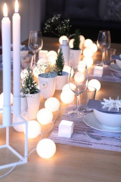 Intertwine a string of white paper lantern lights as a part of your table center piece. (check the wattage and test the lights before dinner to ensure the bulbs wont over heat)
