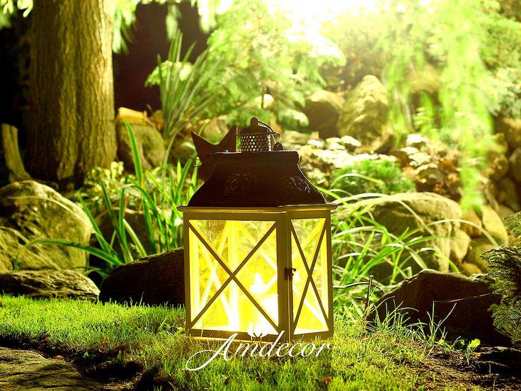 Lanterns at night in a charming garden. Lampion w ogrodzie na trawce. Biały lampion z metalowym daszkiem.