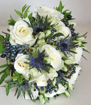 Large headed roses were combined with spray roses, the blue Eryngium, myrtle and viburnum tinus berries to create a hand tied design