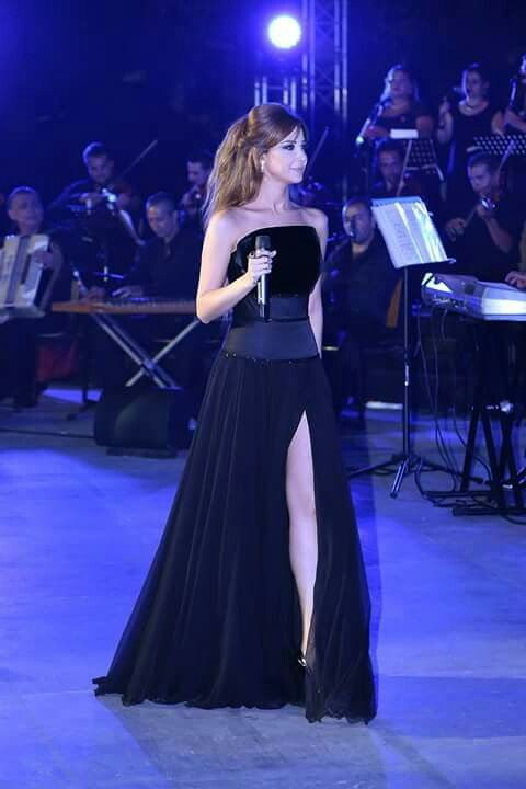 NANCY Ajram wearing long black dress with acut . From Ralph &Russo