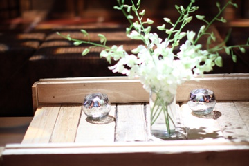 Smaller arrangements of white orchids were placed in the lounge areas, this one atop a found crate that was cleaned and sanded before being used as a coffee table for guests.