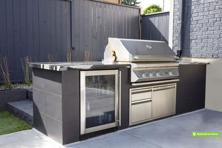 Outdoor cooking is made easy with this custom BBQ station beautifully clad in charcoal porcelain tiles and granite countertop. The premium Twin Eagles stainless steel grill with built-in fridge and drawer system are conveniently positioned to assist the outdoor chef.