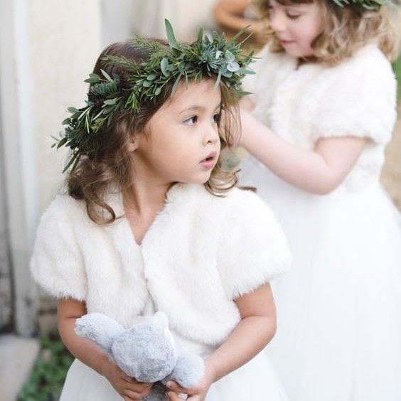 Adorable flower girls wrapped up warmly in their fur boleros for a winter wedding as seen on @stylemepretty / Image by @nicola_stegmann