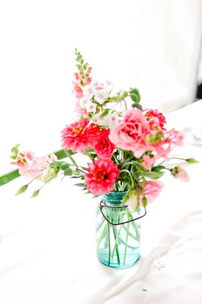 Great example of vibrant locally grown flowers: zinnias, lisianthus, snapdragons, and phlox in a blue mason jar.