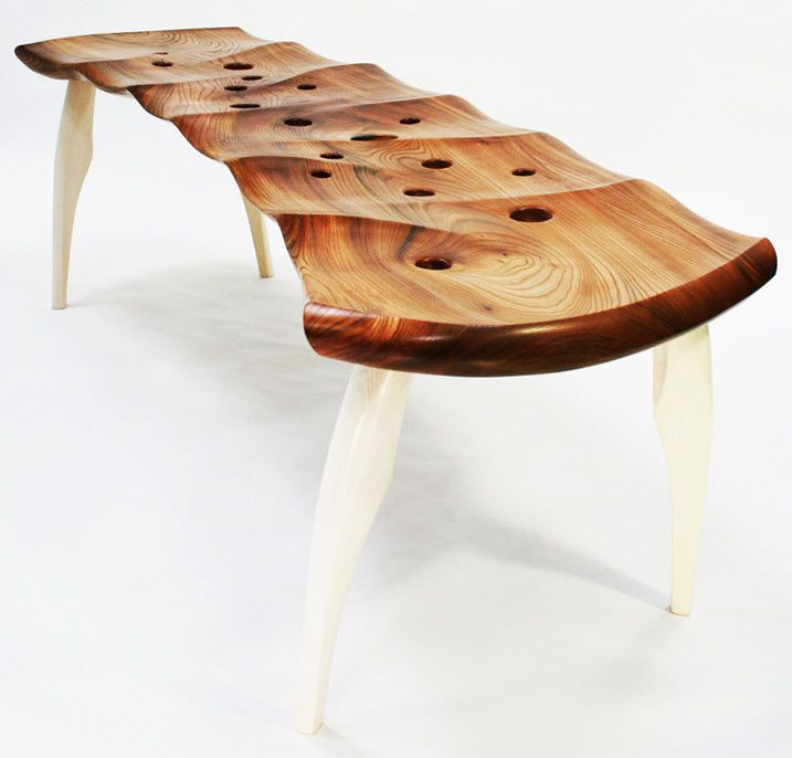 The Razorfish Bench seat is made from a single slab of elm wood that has been carved into a series of interlocking hollows inspired by the hidden life on a sandy ocean beach