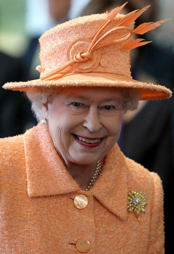 Queen Elizabeth beams like a Creamsicle on a visit to Gordonstoun school in Scotland, where her majesty christened a new sports facility. She chose her Frosted Sunflower Brooch, which she prefers to wear with orange.