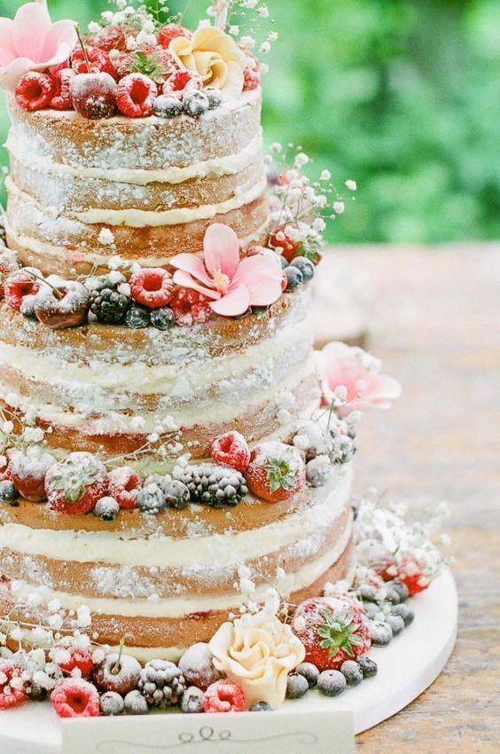 Schöner nackter Kuchen bestäubt mit Puderzucker, Blumen und Beeren. – Hochzeit …   – Hochzeitskleid