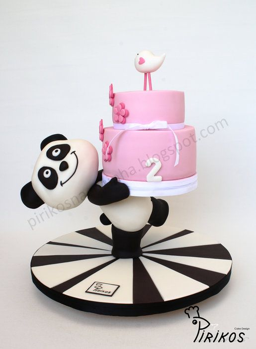 Un soporte de la torta hecha por nosotros y cubierto de pasta de azúcar, con un pequeño pastel en la parte superior.