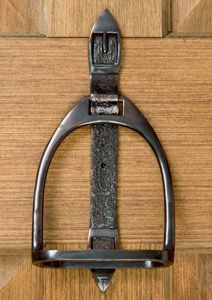 Stirrup and a piece of leather used as a door knocker--love this!