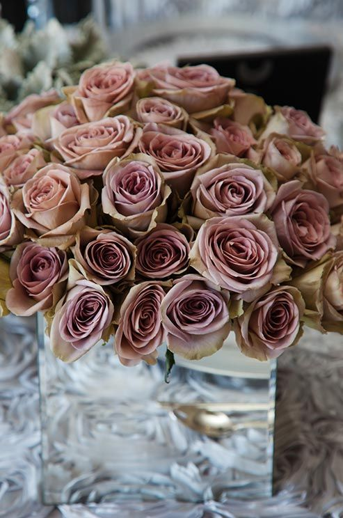 Dusty pink antique roses bring vintage flair to a modern square mirrored vase.