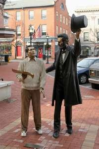 A statue of Abraham Lincoln talking with a visitor stands outside the David Wills House in Downtown Gettysburg.