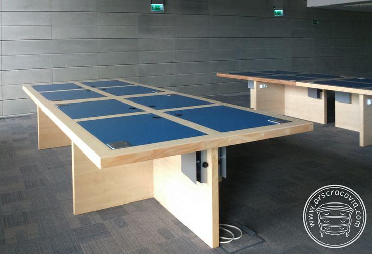 Multimedialne stoły do czytelni w bibliotece, wykonane z laminatów HPL i litego drewna, w panelowych nogach rozprowadzono okablowanie i zamontowano gniazda zasilające. Kolorystyka blatów odpowiada poszczególnym działom biblioteki.