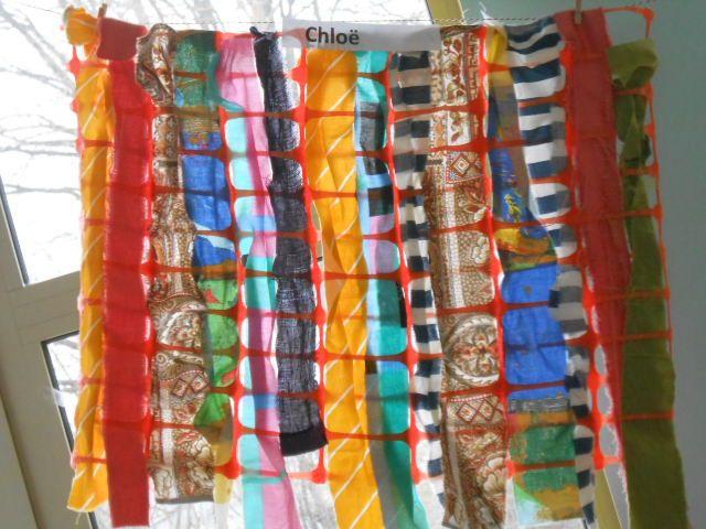 kleuters weven repen stof door oranje werfafsluiting.