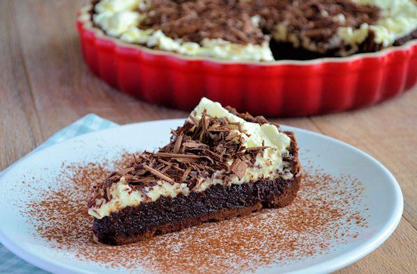 Een krokante chocolade koekbodem en smeuïge chocoladevulling bedekt met een frisse laag slagroom, die weer gegarneerd is met chocoladekrullen.