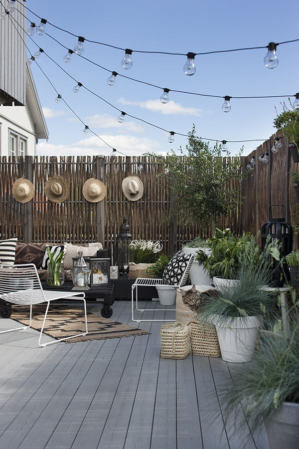 Cute little outdoor setup. Sun hats hung on the fence make a thoughtful addition for daytime users, while lovely string lights provide atmosphere in the evenings.