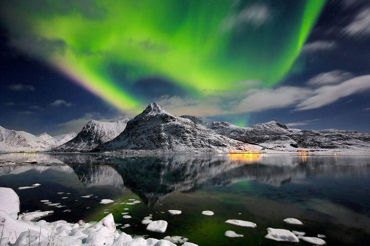 Image: Aurora boreal en las islas de Lofoten, con montañas nevadas refleja en el mar