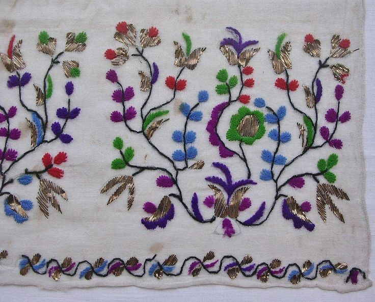 Detail of a napkin, Crimean Tatar, from Turkey, 1870-1920.  Embroidered on cotton (muslin), 58 x 69 cm.  Featuring a 'Tree of Life' motif with flowers and leaves, worked in double running and satin stitches in colors of green, red, blue, purple, fuchsia, black & metallic (golden) strips, worked in 'telkırma'-technique.  The motif repeated 3 times along width of cloth.  Height of the embroidery (from the tip of flowers to the end of cloth): 19 cm.  (The Asiye-Zeynep Collection, Washington…