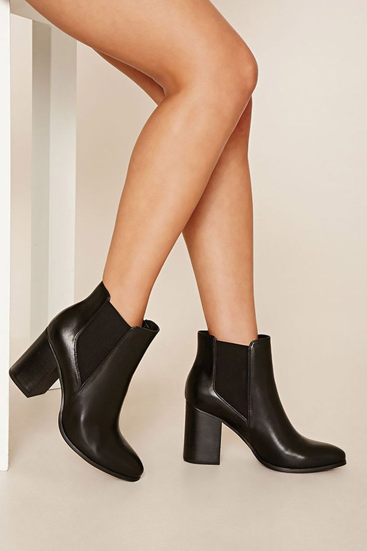 A pair of faux leather chelsea boots with a block heel, an elasticized gore, and a slightly pointed toe.