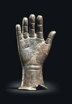 A ROMAN BRONZE VOTIVE RIGHT HAND CIRCA 2ND-3RD CENTURY CE. Naturally modeled with palm and fingers outstretched, nails, delineated palm lines and creases across wrist and fingers, dedication in Greek across palm reading: 'NABOYSAME EUZAMENOS AN[E]THEKEN', translating as 'Nabousame, having made a vow, dedicated [this]'.