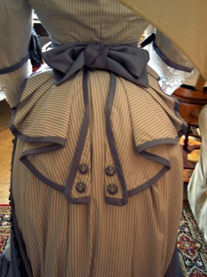 close up of pleating details on jacket, backside, bustle. trimmings, buttons, bow. embellishments.