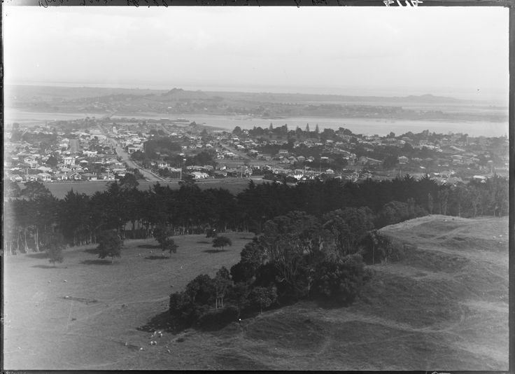 1931. Looking south from One Tree Hill across Onehunga, (left), and Royal Oak, (right), towards the Manukau Harbour and Mangere showing Mangere Mountain, (left of centre background), Mangere Bridge, Campbell Road, (left to right across centre), Queen Street, (diagonally left), then Selwyn Street, (diagonally centre), Jellicoe Park, (right of centre), and Tiwai Road, (centre) off Campbell Road. Sir George Grey Special Collections, Auckland Libraries, 4-4774.
