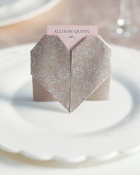 The ancient art of Japanese paper folding was used to make this romantic design, complete with a pocket for a place card. Making the 3 1/4-inch stand-up heart shape is surprisingly simple. Choose 6-inch square origami papers with a pretty pattern or different color on each side; both will be visible in the heart.