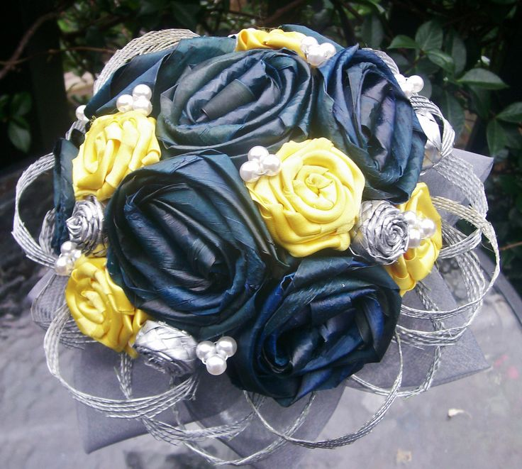 Hand dyed and woven blue flax roses with yellow satin roses and silver plaited flax buds. Accented with pearls and silver flax netting