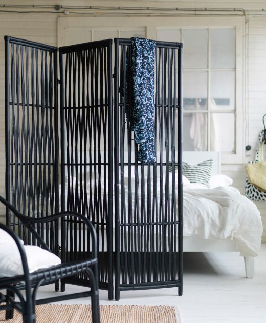 A black room divider made of rattan/bamboo, shown in a bedroom.