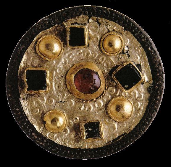 Forme - Fibule ronde mérovingienne en bronze, recouverte d'or et de pâtes de verre découverte dans une nécropole. (VIIe siècle.)