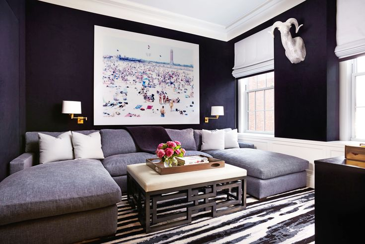 In the den, the walls are upholstered in a dark navy moleskin fabric and the U-shaped sofa adds comfort.