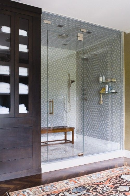 Love this bathroom..the mix of dark wooden cabinets and an oriental rug with a light blue/gray tiled shower. Great combination.