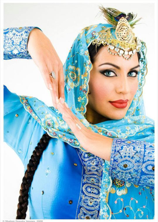 Persian dancer posing gorgeously wearing traditional costume.
