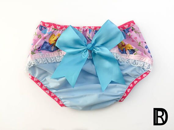 One of a kind special design diaper cover with cute sissy details. The diaper cover features a solid blue waterproof base with pink donkey and bear character floral cotton print, satin lace trim and removable snap-on oversized blue bow. Raspberry heart Fold Over Elastic (FOE) is strategically sewn throughout adding stretch where needed at the waist and legs. You will receive the item shown. If you would like this design in a different style or size please message the shop with your inquiry…
