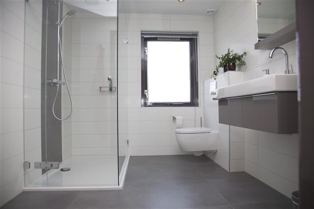 Strakke lijnen tekenen deze bijzonder fraaie badkamer. De asymmetrische indeling van de spiegel in combinatie met de chique kleurstelling van het meubel geeft deze badkamer nóg meer cachet. Last but not least de rond gevormde radiator met een bijpassende, rond gevormde handdoekhouder als kroon op het geheel.
