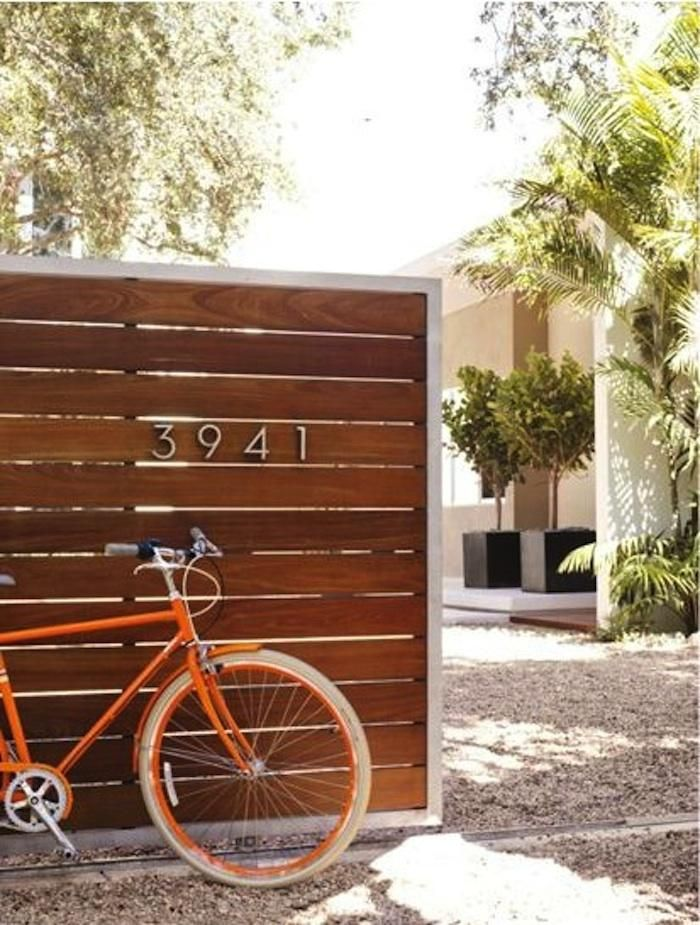 Slatted wooden fence, aluminum Neutra House Numbers & a fabulous orange bike. via Gardenista. source: DWR