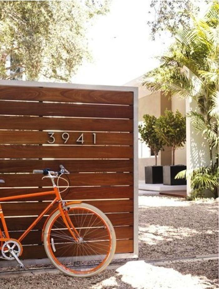 Slatted wooden fence, aluminum Neutra House Numbers & a fabulous orange bike. via Gardenista. source: DWR