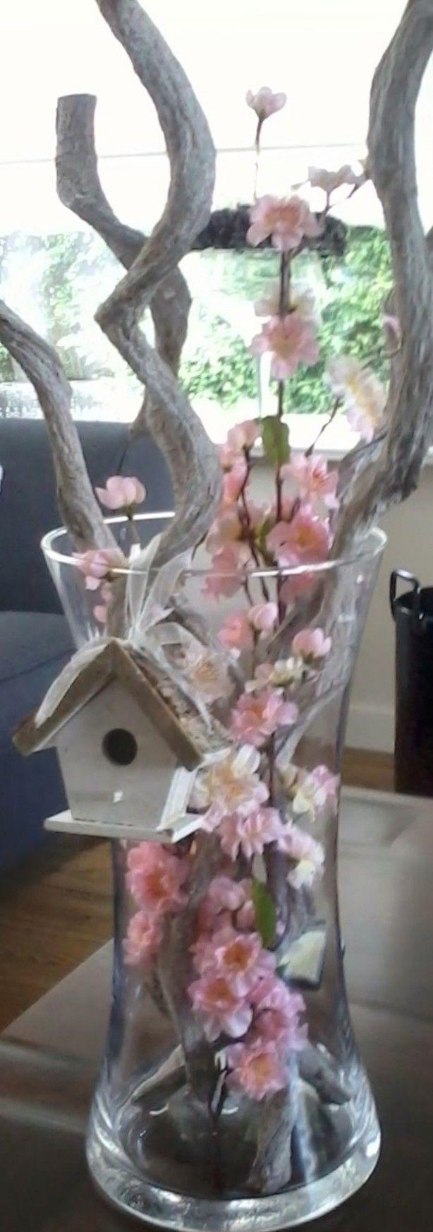Beetje wazige foto, maar het gaat om het idee. Doe een aantal takken in een hoge vaas, (kunnen ook gewoon fruitboomtakken zijn) en stop er wat (kunst) bloemen tussen!