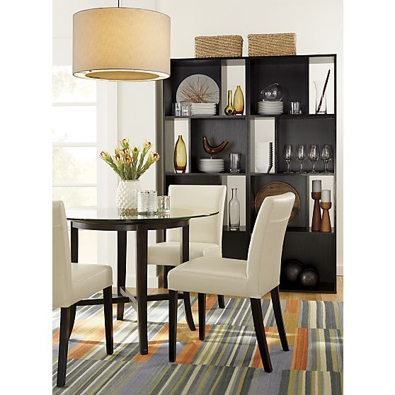 The wood base has a rich deep ebony stain table seats four halo ebony dining table with glass top is a crate and barrel
