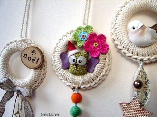 Delle piccole ghirlande fatte con gli anelli in legno (quelli per le tende) ricoperti a uncinetto e decorati con diversi elementi.  La fonte originale è GadenaOverBlog.  E' in francese e non ci