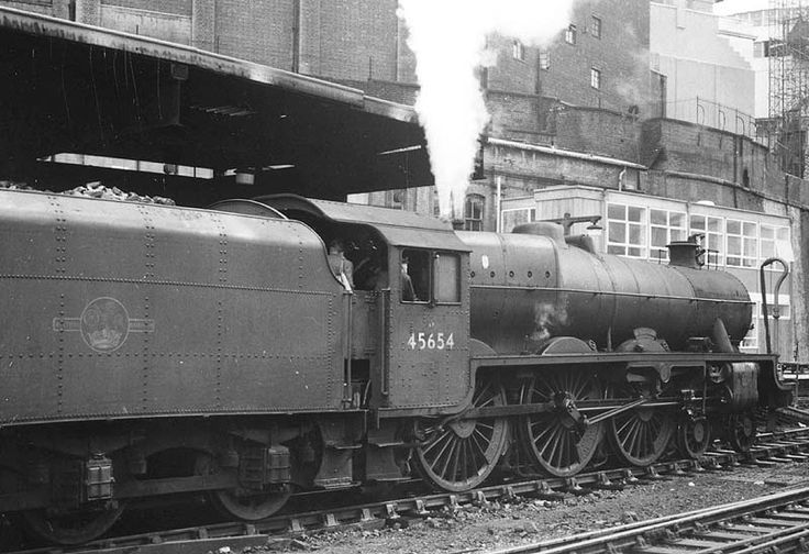 """46554 """" Hood"""".Ex-LMS 5XP 4-6-0 Jubilee class No 45654 'Hood' is seen standing at the East end of Platform 3 at the head of a New Street to Euston express on 8th August 1964. Built as LMS No 5654 by Crewe works in February 1935 No 45654 remained in service until June 1966 when it was withdrawn from Newton Heath shed in Manchester to be scrapped by TW Ward of Beighton near Sheffield although records show it was in store at Staveley shed in January 1962"""