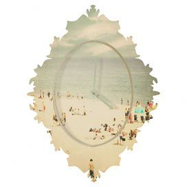 """Showcasing a Baroque-inspired frame and beach scene motif, this chic wall clock makes a stylish statement.   Product: Wall clockConstruction Material: Bamboo, aluminum and steelColor: MultiFeatures:  Baroque-inspired frameDesigned by Shannon Clark for DENY DesignsEco-friendly UV-resistant coating FSC certified bamboo Magnetic and hidden floating frame Made in the USA  Accommodates: (1) C Battery - not includedDimensions: Small: 19.5"""" H x 14.5"""" W x 1.5"""" DMedium: 29.2"""" H x 21.7"""" W x 1.5"""" ..."""