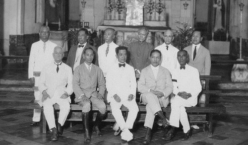General Aguinaldo (seated, center) and ten of the delegates to the first Assembly of Representatives that passed the Constitucicn Politica de la Republica Filipina on January 21, 1899 Picture taken in the Barasoain Church, Malolos, December 8, 1929. Via Wikimedia Commons.