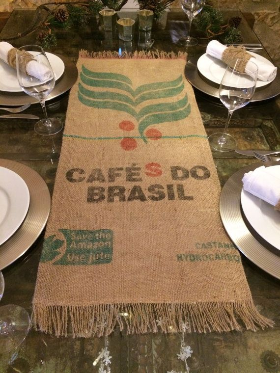 Add some eco-chic to your table with this hessian table runner. This reversible, fringed table runner is handcrafted using recycled coffee sacks on one side and pre-loved fabric on the other. All materials used are 100% recycled or upcycled. This would make the perfect gift. The designs on each table runner vary slightly as shown in the photos. The table runner measures approx. 37 x 15 inches (94 x 38cm). Product care: The fabrics used have already been washed, hereafter we recommend spot...
