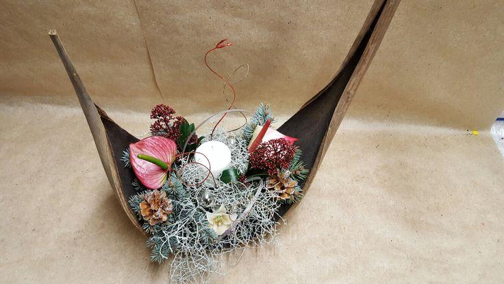 Centro tavola su foglia di cocco con fiori e piante invernali..