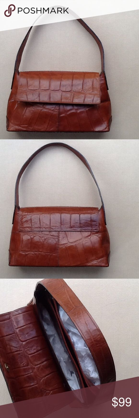 JOAN & DAVID POCKETBOOK This beautiful Joan & David pocketbook is BRAND NEW, and has never been used. The pocket book is a perfect shade of golden brown with a reptile embossed print. The front has a snap that closes on the outside. The inside has two compartments and a third zipper compartment in the middle. The dimensions are 8 inches high, 12 inches wide and 4 inches across the bottom.A medium sized handle makes it perfect for carrying over your shoulder or hanging on to with the hand…