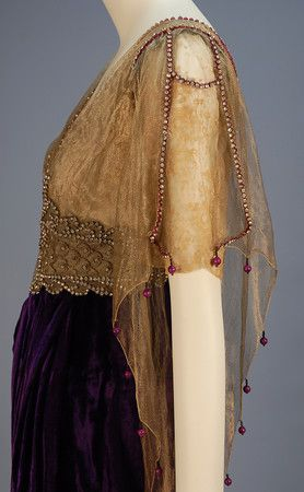 "Dress 1910s Whitaker Auctions; (sleeve detail) | TRAINED VELVET BELLE EPOCH GOWN with JEWELED BODICE 1913. Lush royal purple panne silk having short sleeve silk lace V-neck bodice asymmetrically draped in gold metallic mesh, high jeweled midriff band with center clear and magenta paste butterfly, hobble skirt layered over short train. Label ""Joseph 632 Fifth Avenue New York CYCLAMEN"""