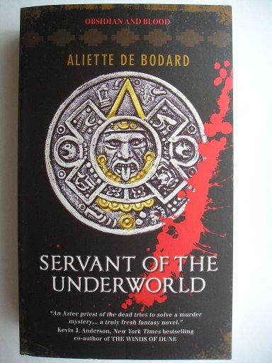 "The novel ""Servant Of The Underworld"" by Aliette de Bodard was published for the first time in 2010. It's the first in the ""Obsidian And Blood"" series. Cover by Spring London for an American edition. Click to read a review of this novel!"