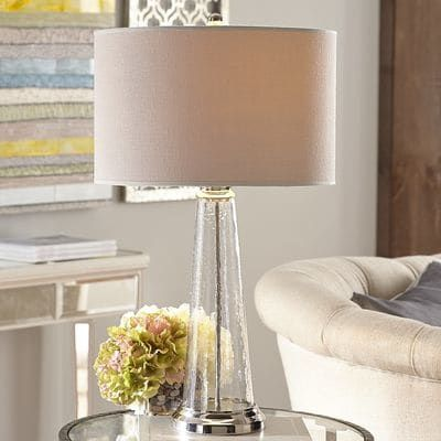 Clearly, you have good taste. Handcrafted with a modern tapered silhouette, natural linen shade and hammered texture, this clear glass lamp has a penchant for versatility. When paired with your room's existing decor, you'll see it all again in a brand new light.