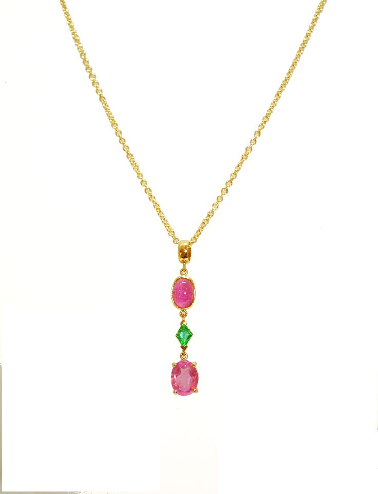 This 19ct gold necklace features two clear pink Topaz and a vibrant green garnet.